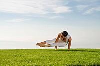 Young woman practising Hatha yoga outdoors, showing the pose kakasana, bakasana, dvi-pada-koundinyasana, variation of crow pose, Nove Mesto, Okres Tep...