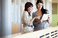 Two businesswomen looking at a computer tablet.