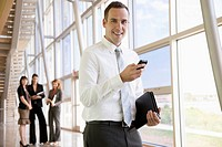 Businessman stands in an office lobby and uses his cellphone.