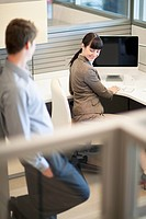 Businesswoman smiles back at a male co_worker from her cubicle.