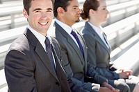 Three businesspeople sit together on bleachers.