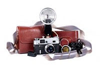 Set of old camera with flash, extra lens and covers isolated over white background