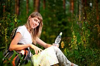 beautiful young woman sitting on forest floor with backpack, map and bottle of water, smiling and looking in camera