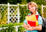 beautiful young student girl with backpack standing in campus park, holding books, smiling and looking into the camera
