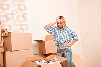 Moving house: Young woman unpacking box with kitchen dishes