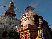 Old woman performing a religious ceremony in front of Boudnath stupa, Boudnath, Kathmandu, Nepal, South Asia
