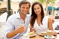 Young Couple Enjoying Coffee And Cake In CafŽ