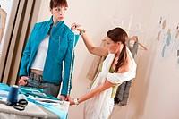 Female fashion designer measuring turquoise jacket on model, taking measurements