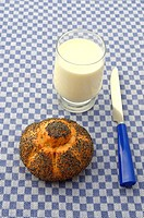 Poppy seed roll, glass of fresh milk, breakfast knife