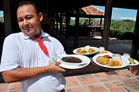 near Filadelfia Costa Rica: waiter serving the lunch at Hacienda El Viejo
