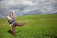 Mother and son on a grassy slope in the Alps, Italy