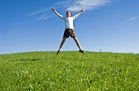 Young woman jumping with joy on a grassy hill in Nova Ponente, Alto Adige, Italy