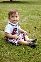 Young Boy Sitting in Grass, Portrait