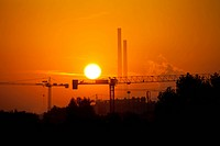 Industrial site, silhouettes with chimneys and cranes at sunset