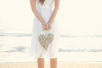 Hispanic woman holding large, woven heart on beach