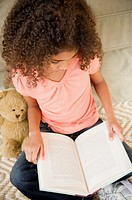 Mixed race girl reading book
