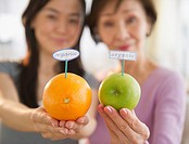 Japanese mother and daughter holding fruit with organic label
