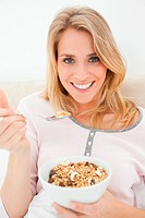 A close up shot of a smiling woman as she has a raised spoon of cereal in her hand
