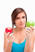 Serious teenager holding a green apple and a red one