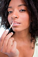 Young woman applying gloss in a concentrated way against a white background