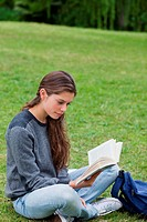 Young woman sitting on the grass while crossing her legs and reading a book