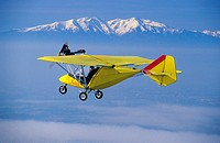 Ultra light plane flying in wintertime over thin clouds around Torreilles  At background the snowed Canigou peak 2784 m  Eastern Pyrenees, Languedoc R...