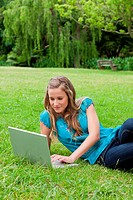 Young calm girl lying on the side on the grass while working on her laptop in a park
