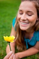 Beautiful yellow flower held by a smiling young woman