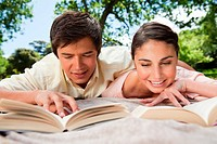 Man and a woman smiling while reading books together as they are lying prone on a blanket in the grass
