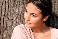 Woman sitting against a tree while looking towards her left as the sun is shining on her face