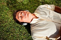 Man closes his eyes as he uses headphones to listen to music while he lies down on the grass