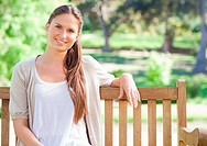 Smiling young woman sitting on a park bench