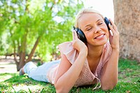 Young woman wearing headphones while lying on the lawn