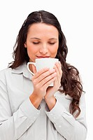 Brunette smelling a tea against white background