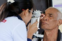 Eye clinic. Cataract surgery patient having his eye checked the day after surgery. Photographed at a mobile clinic in Bali, Indonesia.
