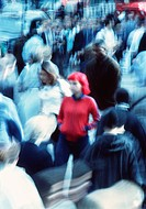 Crowd. Blurred image of a woman standing in a crowded city street.