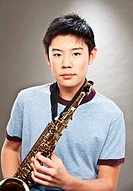 Portrait of young Asian teenage boy holding saxophone