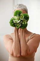 Senior woman holding plant in front of face