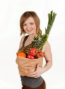 Young woman holding a bag of fruits and vegetables