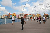 People on the Queen Emma Bridge, eastern district of Punda, trading arcade in the historic district of Little Amsterdam, as Willemstad is also known a...