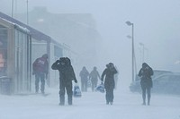 Passers-by in a snow-storm in the centre of the village of Longyearbyen, Spitsbergen, Svalbard, Norway, Europe