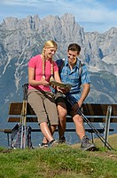Hikers sitting on a bench on Hartkaiser mountain, Wilder Kaiser mountain at the back, Tyrol, Austria, Europe