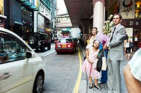 A family dressed up for an event waits for a taxi in Central, Hong Kong
