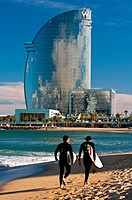 Surfers walking on the beach with W Barcelona Hotel in the background, Barcelona, Catalonia, Spain