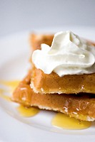 Hot, fresh waffles drizzled with syrup and topped with whipped cream