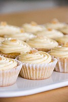 A tray of ginger cupcakes with icing