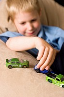 A young boy plays with some small toy cars