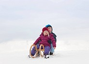 Children sitting on sled in snow