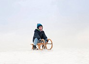 Boy sitting on sled in snow