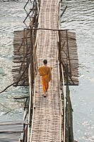 A young Buddhist monk walks across a bamboo bridge in Luang Prabang Laos